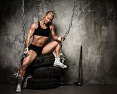 stock photo of muscle builder  - Beautiful muscular bodybuilder woman sitting on tyres and holding chains - JPG