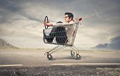 stock photo of trolley  - businessman driving with a shopping cart on the road - JPG