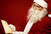 stock photo of letters to santa claus  - Portrait of Santa Claus looking at Christmas letter in his hands - JPG