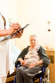Young nurse and female senior in nursing home, measurements are taken or administrative duties taken