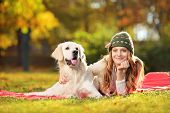 stock photo of labradors  - Pretty female lying down with her labrador retriever dog in a park - JPG