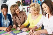stock photo of thread-making  - Group Of Women Making Quilt Together - JPG