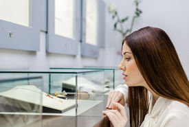 foto of jewel-case  - Close up view of girl looking at jewelry in window case at jeweler - JPG