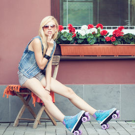 stock photo of roller-derby  - Young blonde woman in roller skates sitting on the chair - JPG