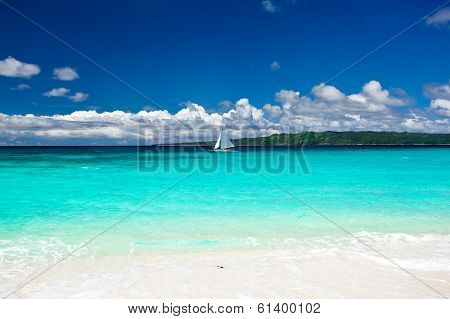 Beach With Sailboat In Ocean