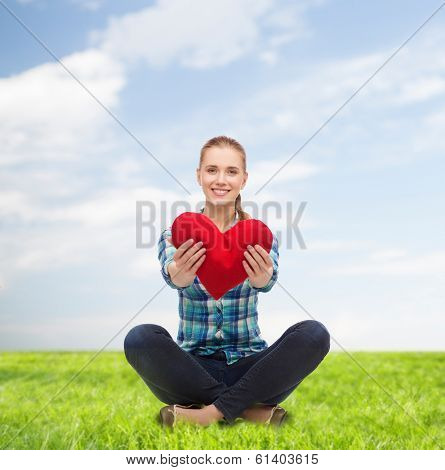 happiness and people concept - smiling young woman in casual clothes sitiing on floor and holding red heart