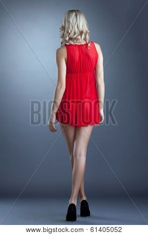Slim girl posing in red negligee, back to camera