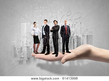 Conceptual image of business team on standing on palm