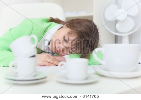 Woman Has Got Tired And Sleeps On Table Among Coffee Cups