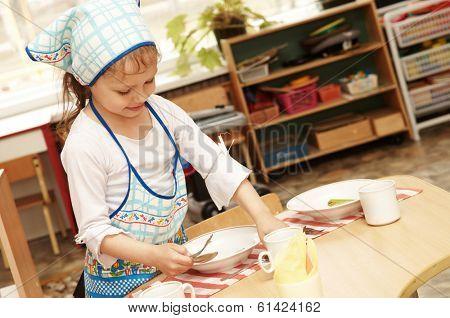 little girl serving foor breakfast at kindergarten