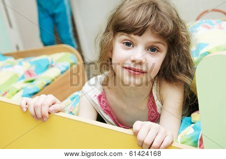 Portrait of little girl in bed preparing to sleep in in kindergarten