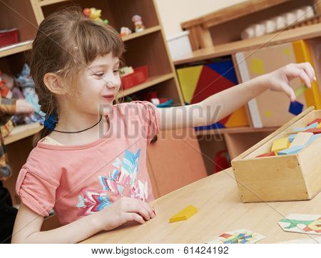 smiling laughing little girl playing in development game at kindergarten