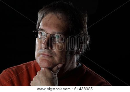 Mature Man Looks Quizzical - On Black Background With Dramatic Lighting