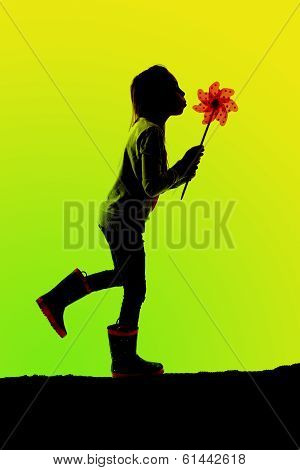Silhouette Of Girl Walking Blowing A Toy Pinwheel Greeen Background