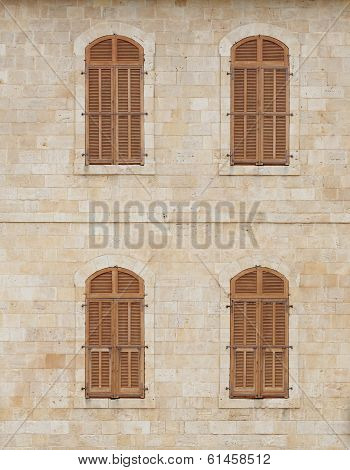 Wall of the old building with closed windows covered by wooden blinds