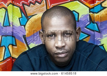 Handsome Afro man in front of a graffiti wall