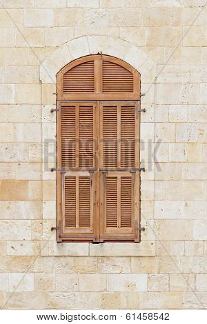 Closed window of the old building covered by wooden blinds