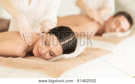 healthcare and beauty concept - picture of couple in spa salon getting massage