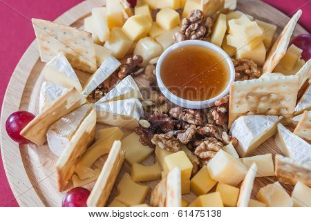 Different Varieties Of Cheese With Grapes, Crackers, Nuts And Honey On Wooden Plate
