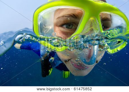 Extreme close up underwater portrait of a woman with mask snorkeling in a sea
