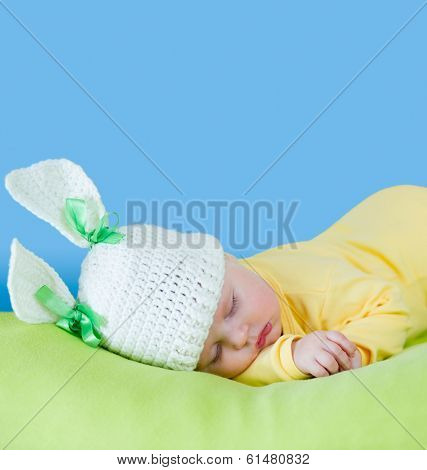 sleeping baby closeup portrait in hare or rabbit hat with expandable blue copyspace