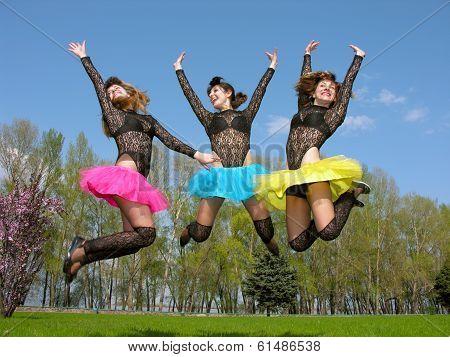 Three Cheerful Showgirls Jumping Outdoors