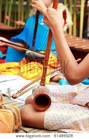 A Girl Plays A Local Thai Music Instrument.