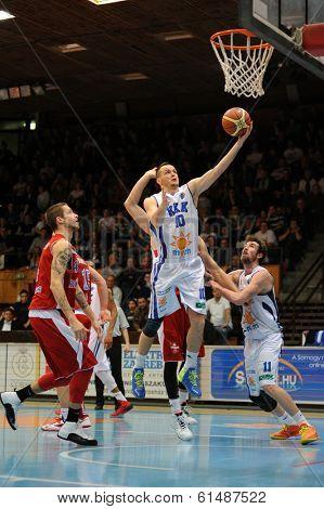 KAPOSVAR, HUNGARY - MARCH 8: Branislav Jancsikin (white 10) in action at a Hungarian Championship basketball game with Kaposvar (white) vs. Paks (red) on March 8, 2014 in Kaposvar, Hungary.