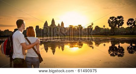 Couple at Angkor Wat temple complex in sunrice, near Siem Reap, Cambodia.