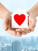 charity, real estate and family home concept - closeup picture of female hands holding white paper h