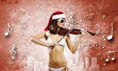 Young Santa girl in bikini playing violin