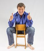 Man Sits On A Small Wooden Chair And Shows Thumbs Up Sign