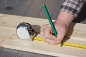 Measuring A Wooden Board With Ruler And Pencil.