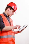 stock photo of vest  - Young man construction worker builder in orange safety vest and red hard hat using tablet touchpad isolated on white - JPG