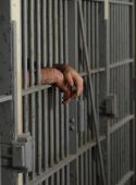 stock photo of jail  - mans hands behind bars in jail or prison