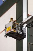 stock photo of cherry-picker  - color photo of firefighter lifted in cherry picker in fire rescue - JPG
