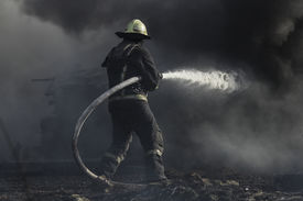 picture of firemen  - Fireman spraying water in a smouldering burnt out house - JPG