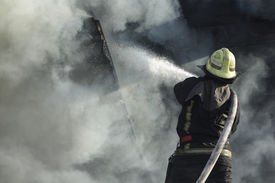stock photo of firemen  - Fireman spraying water in a smouldering burnt out house - JPG