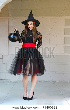 A young pretty witch poses with Halloween props