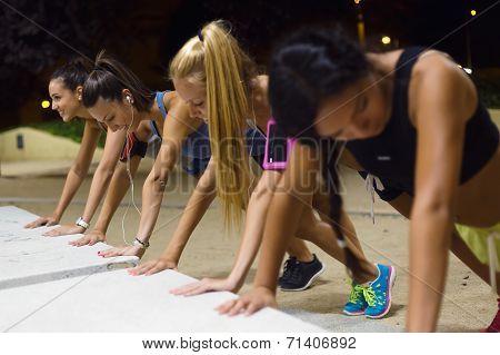 Group Of Girls Doing Push-ups At Night.