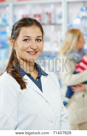 cheerful female pharmacist chemist woman portrait in pharmacy drugstore