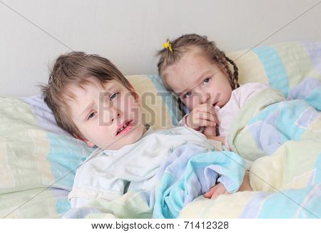 Two diseased children with flu lying in the bed.
