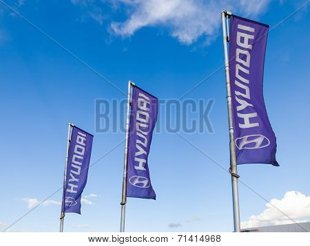 Samara, Russia - August 30, 2014: The Flags Of Hyundai Over Blue Sky. The Hyundai Motor Company Is A