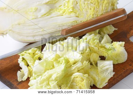 detail of chopped chinese cabbage and kitchen knife on wooden cutting board