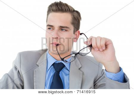 Nerdy businessman holding pen looking away on white background