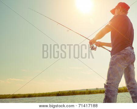 Young man fishing at sunny day