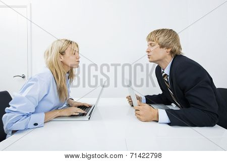 Side view of business couple kissing in office