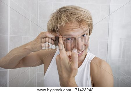 Portrait of man squeezing pimple on his forehead in bathroom
