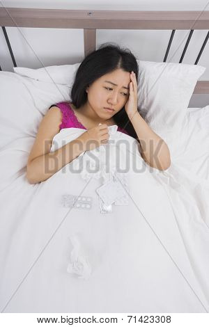 Young woman suffering from cold and headache lying in bed