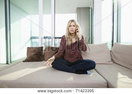 Full length of young displeased woman talking on mobile phone at home